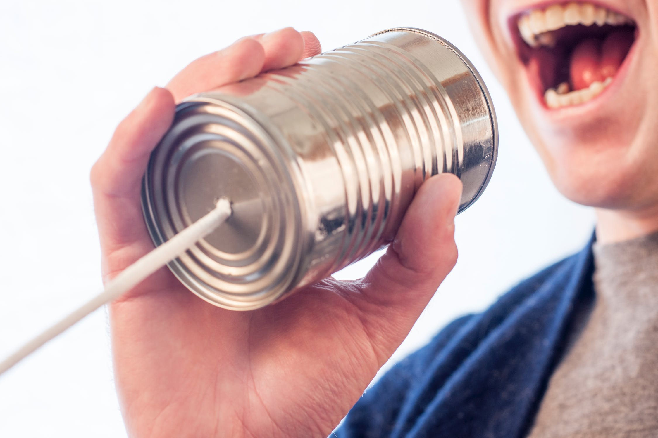 Person speaking to a can with a string as a pretend telephone.