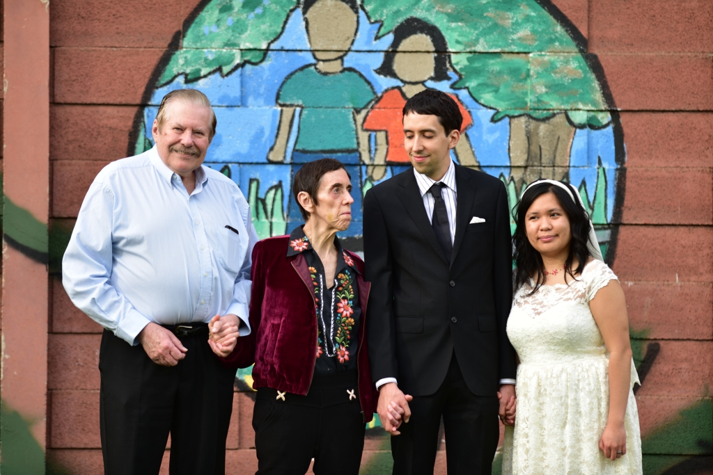 A group of four people photographed together, mother, father, groom, and bride