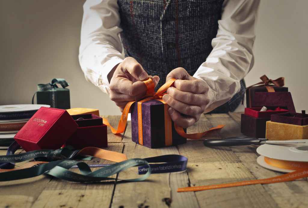Man wrapping a gift box, tying the ribbon.