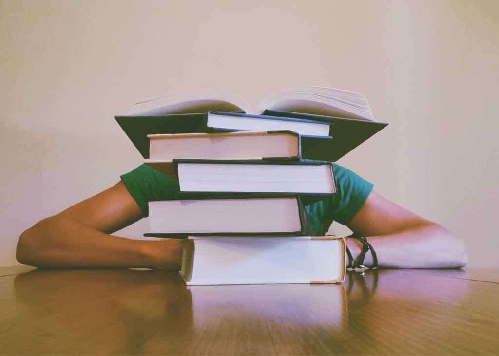 stack of books on a table with a person behind the stack, showing only their arms and shoulders