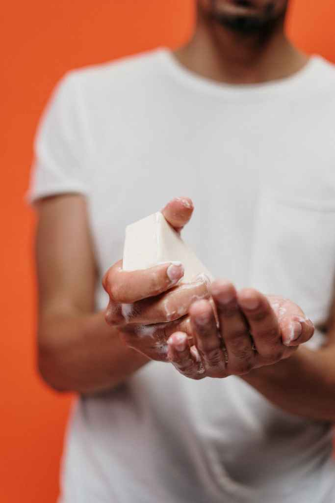 Person wearing white shirt soaping hands with white bar of soap