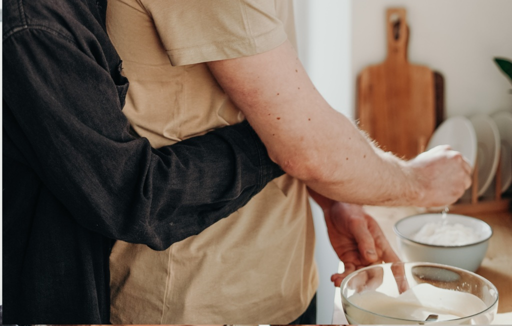 Close up of a couple mixing baking ingredients. One person hugging the other from the back.