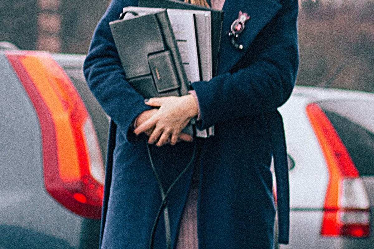 closeup of a female student carrying books while standing on a sidewalk with parked cars