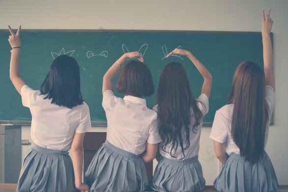 Four high school students in uniforms, standing in front of the classroom by the blackboard,making silly hand gestures.