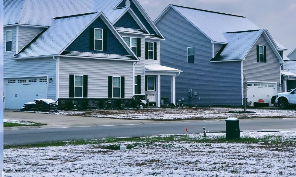 Two 2-storey homes beside each other with the  grassy lawns frosted with snow