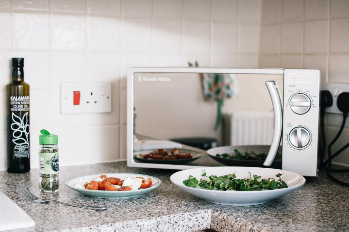 Kitchen counter with a microwave, sauce with tomatoes, a plate with greens and bottle of spices and olive oil