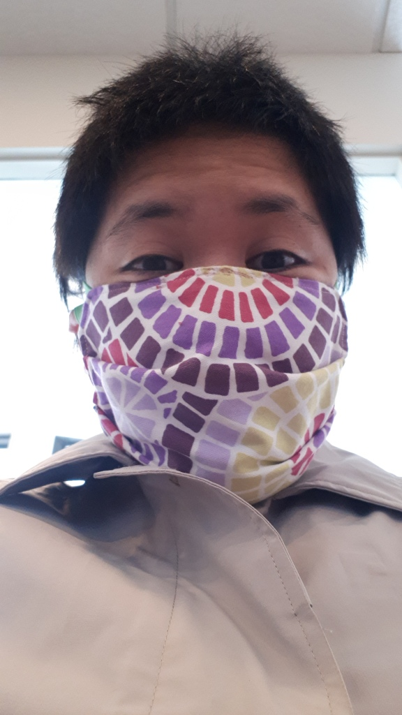 Selfie of woman wearing a fabric face mask, the horizontal accordion style.