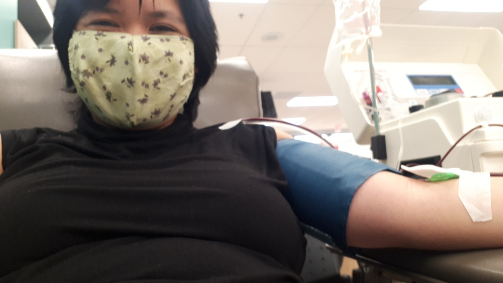 Woman wearing a face mask while donating blood at a blood donation clinic.