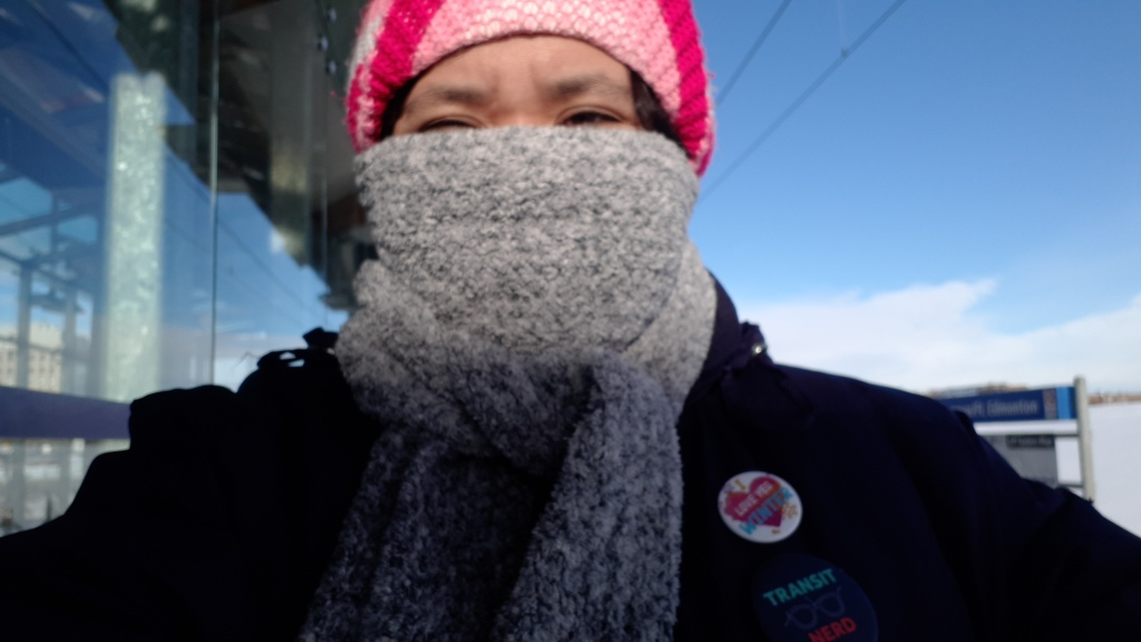 Selfie of woman outside in winter, wearing a knitted winter hat and most of her face covered in a light blue scarf