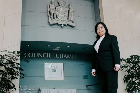 Woman in business suit standing in front of the entrance of Edmonton City Hall Council Chambers.