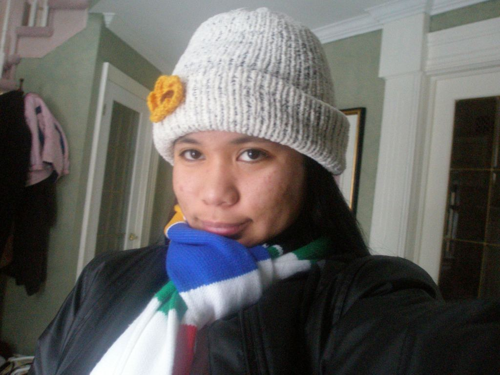 Woman wearing a black winter jacket, multi color scarf and white knitted hat with a yellow knitted flower.